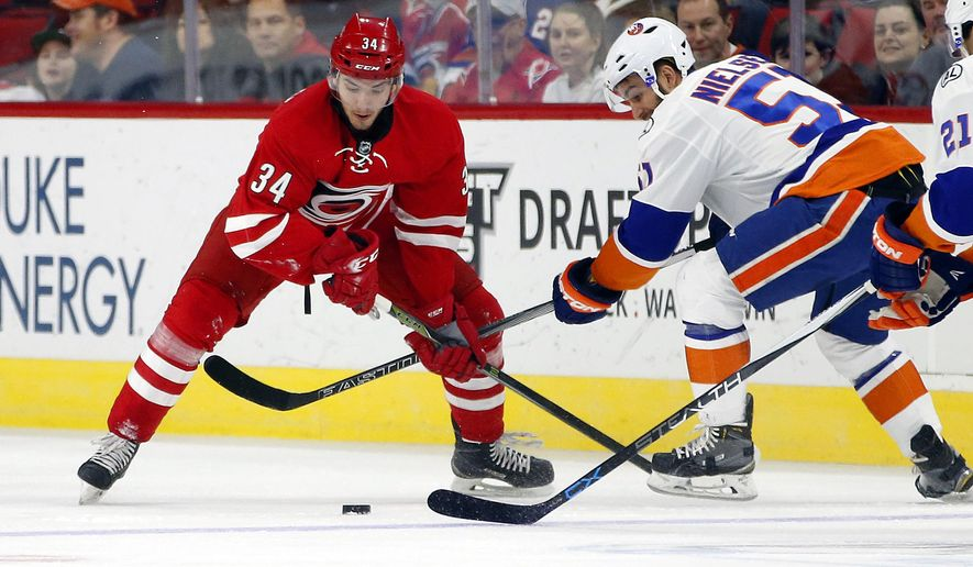 Carolina Hurricanes' Phil Di Giuseppe (34) battles with New York Islanders' Frans Nielsen (51) during the first period of an NHL hockey game, Saturday, Feb. 13, 2016, in Raleigh, N.C. (AP Photo/Karl B DeBlaker)