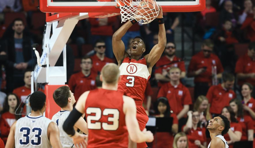 Nebraska's Andrew White III (3) dunks over Penn State's Shep Garner (33), Deividas Zemgulis, second left, and Josh Reaves, right, during the first half of an NCAA college basketball game in Lincoln, Neb., Saturday, Feb. 13, 2016. (AP Photo/Nati Harnik)