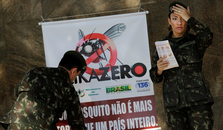 "Soldiers set up a sign that reads in Portuguese, ""A mosquito is not stronger than an entire country."" More than 200,000 troops are fanning out across Brazil to show people how to eliminate the mosquito that spreads the Zika virus. (Associated Press)"