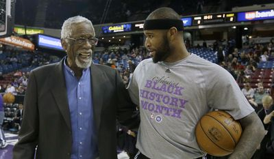NBA legend  Bill Russell, left, talks with Sacramento Kings center DeMarcus Cousins before the Kings played the Dallas Mavericks  in an NBA basketball game in Sacramento, Calif., Thursday,  Feb. 5, 2015.(AP Photo/Rich Pedroncelli)