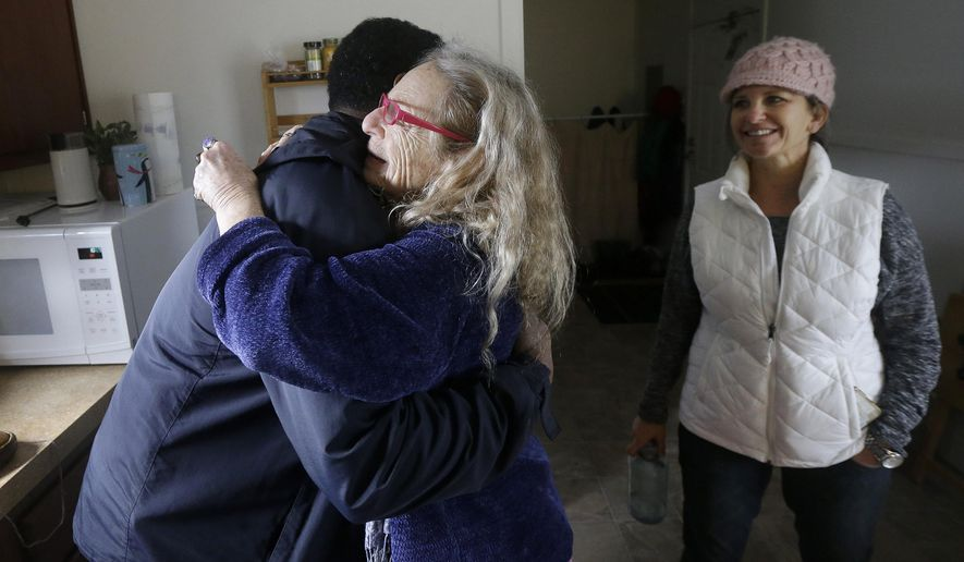 In this Tuesday, Jan. 19, 2016 photo, Lorindra Frances, a spiritual healer who lived at Harbin Hot Springs before it closed after September 2015 wildfires, center, hugs Federal Emergency Management Agency (FEMA) spokesman Victor Inge as Dena Barron, co-owner of Lake Village Estates, watches in Frances's housing unit in Clearlake Oaks, Calif. Five months after a Northern California wildfire killed four and wiped out homes, many Lake County residents face personal and logistical hurdles that put full recovery years away, if ever, for some. (AP Photo/Jeff Chiu)
