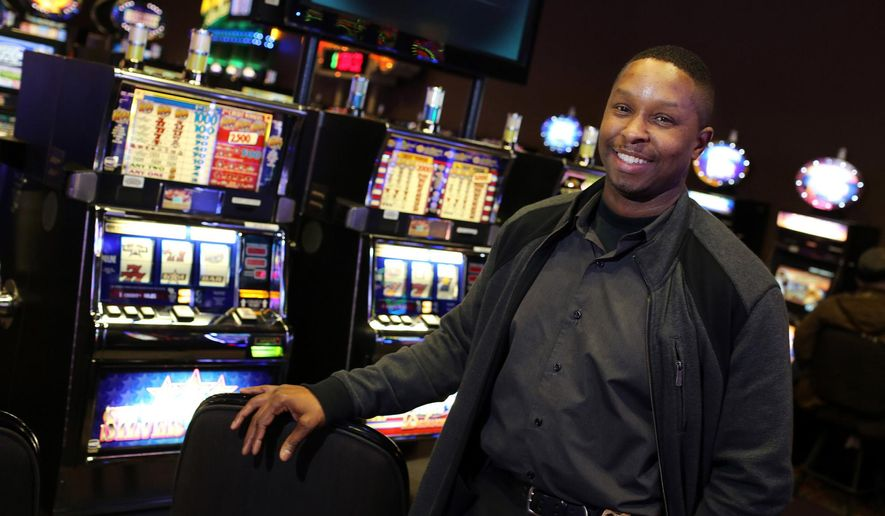 """Tobias Lunsford, a special agent with the Iowa Division of Criminal Investigation, poses for a photo at the Catfish Bend Casino in Burlington, Iowa, on Wednesday Feb. 3, 2016. Lunsford says it's his job, """"To protect the integrity of gaming, both for the players and the state."""" (John Lovretta/The Hawk Eye via AP)"""