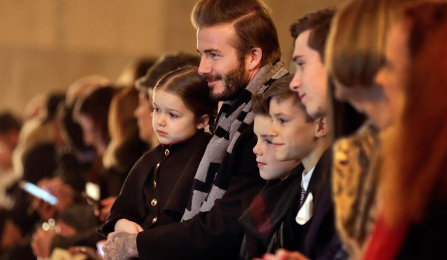 David Beckham and his children wait for the the Victoria Beckham Fall 2016 collection to be modeled during Fashion Week in New York,  Sunday, Feb. 14, 2016. (AP Photo/Richard Drew)