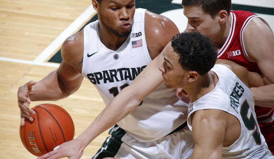 Indiana's Nick Zeisloft, right rear, reaches in to foul Michigan State's Marvin Clark Jr., left, as Michigan State's Bryn Forbes (5) watches during the first half of an NCAA college basketball game, Sunday, Feb. 14, 2016, in East Lansing, Mich. (AP Photo/Al Goldis)