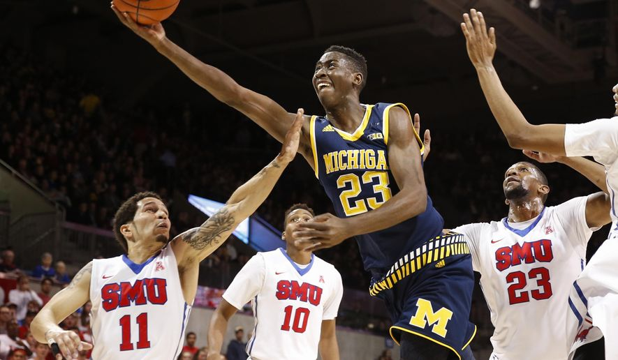 FILE - In this Dec. 8, 2015, file photo, Michigan guard Caris LeVert (23) shoots the ball in front of SMU guard Nic Moore (11) and guard Jarrey Foster (10) during the first half of an NCAA basketball gamein Dallas. Now that he's been able to return to the court, the question is how soon LeVert will get back in game shape for Michigan. By (AP Photo/Jim Cowsert, File)
