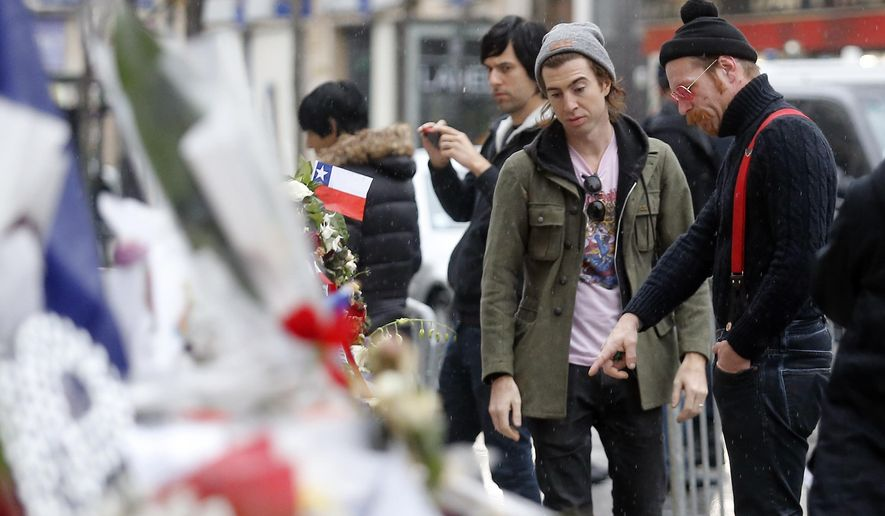 FILE - In this Dec. 8, 2015 file photo, members of the band Eagles of Death Metal, Jesse Hughes, right, and Julian Dorio pay their respects to 89 victims who died in a Nov. 13 attack at the Bataclan concert hall in Paris, France. The Eagles of Death Metal band is scheduled to play at the Olympia Theatre in Paris on Tuesday, Feb. 16, 2016 - just a little over three months to the day since the Paris attacks. (AP Photo/Jacques Brinon, File)