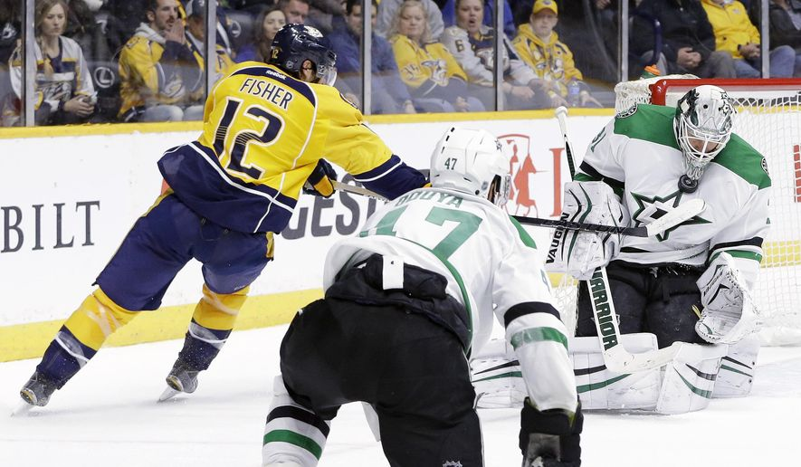 Dallas Stars goalie Antti Niemi, of Finland, holds the puck in place with his mask as Nashville Predators forward Mike Fisher (12) reaches for a possible rebound in the second period of an NHL hockey game Monday, Feb. 15, 2016, in Nashville, Tenn. (AP Photo/Mark Humphrey)