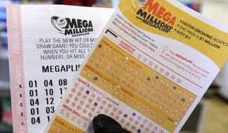A customer holds a Mega Millions lottery ticket at a convenience store in Chicago. (Associated Press)