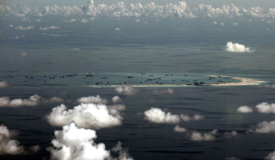 An aerial photo taken through a glass window of a military plane on May 11, 2015, shows China's alleged ongoing reclamation of Mischief Reef in the Spratly Islands in the South China Sea. (Associated Press)