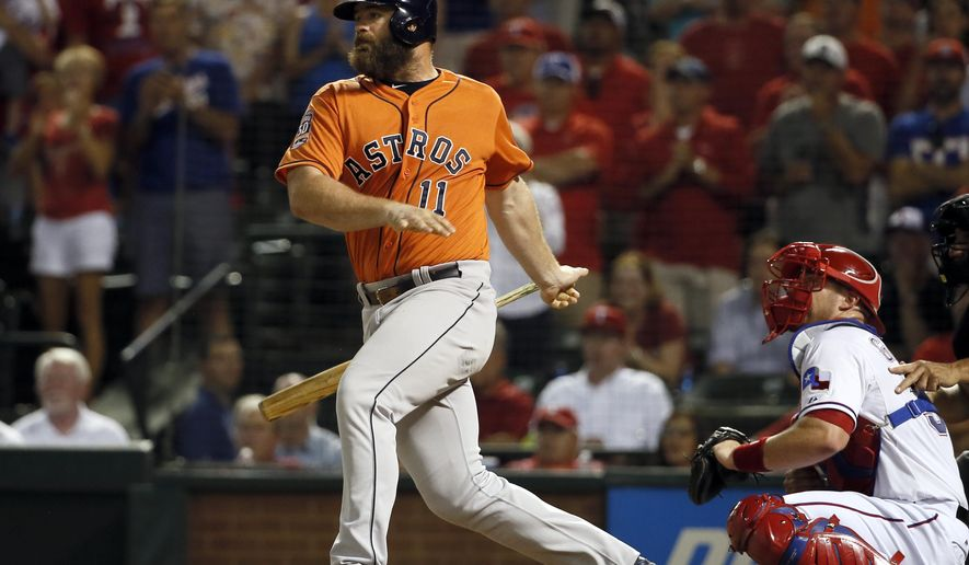 FILE - In this Sept. 15, 2015, file photo, Houston Astros' Evan Gattis follows through on a two-run single as Texas Rangers catcher Chris Gimenez watches during the fourth inning of a baseball game in Arlington, Texas. Injured Houston designated hitter Evan Gattis and the Astros have avoided salary arbitration by agreeing to a $3.4 million, one-year contract. The deal, reached before a scheduled hearing Tuesday, Feb. 16, 2016, calls for a $3.3 million salary this year and includes a $5.2 million club option for 2017 with a $100,000 buyout.(AP Photo/Tony Gutierrez, File)