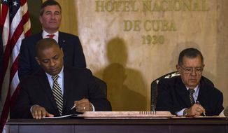United States Transportation Secretary Anthony Foxx and Cuba's Minister of Transportation Adel Yzquierdo Rodriguez, right, sign the airline transportation agreement as Assistant Secretary of State for Economic and Business Affairs Charles Rivkin, top left, looks on in Havana, Cuba, Tuesday, Feb. 16, 2016. Cuba and the United States signed the agreement that will allow U.S. commercial airlines to begin operating flights to the island and vice-versa for the first time in decades. (AP Photo/Desmond Boylan)