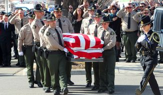 Pallbearers carry the casket bearing the body of Mesa County Sheriff's Department Sgt. Derek Geer on Monday, Feb. 15, 2016, at Canyon View Vineyard Church in Grand Junction, Colo. Geer was shot after responding to a report that a suspicious person carrying a gun and wearing a bandada over his face had been spotted near two schools in Grand Junction last week. (Christopher Tomlinson/Grand Junction Sentinel via AP)