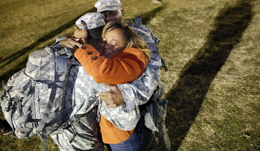 In this Feb. 11, 2016, photo, Tarnisha Gibson, center, hugs her son Spc. Bradley Gibson, left, and husband, Staff Sgt. Corwyn Gibson, during a homecoming celebration at Fort Hood's Cooper Field in Fort Hood, Texas. The Killeen Daily Herald reports the Gibsons are one of the families being reunited after this nine-month deployment of 4,000 soldiers from Fort Hood to South Korea. (Eric J. Shelton/The Killeen Daily Herald via AP)  MANDATORY CREDIT