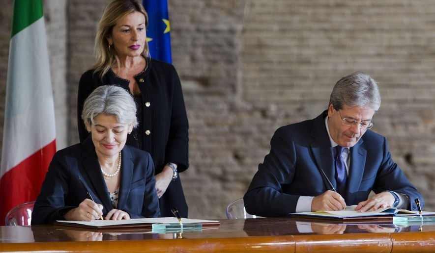 Unesco Director General Irina Bokova, left, and Italian Foreign Minister Paolo Gentiloni  sign an agreement during the presentation of the Unite for Heritage operation in Rome, Tuesday, Feb. 16, 2016. Italy is forming a task force using paramilitary police art experts to prevent the looting and destruction of art and archaeological sites. (AP Photo/Domenico Stinellis)