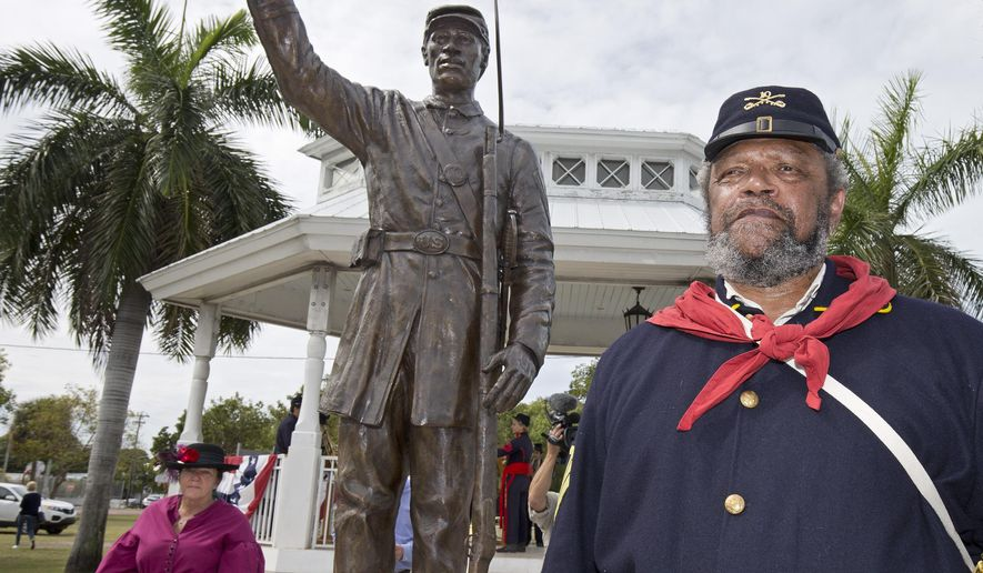 In this photo provided by the Florida Keys News Bureau, Civil War historical re-enactor David Flemming, right, stands by a bronze sculpture Tuesday, Feb. 16, 2016, in Key West, Fla. The sculpture's dedication marked the 153rd anniversary of the 1863 date when more than 120 black soldiers from Key West were instructed to report for duty. (Rob O'Neal/Florida Keys News Bureau via AP)