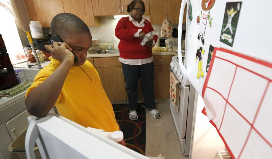 In this Jan. 29, 2016, photo, Debra Aldridge, right, continues to make dinner as her grandson Mario Hendricks talks to a cousin about being able to go to a sleep-over at the cousin's home, at her home on Chicago's South Side. Nationwide, there are 2.7 million grandparents raising grandchildren. About a fifth have incomes that fall below the poverty line, according the Census figures. More grandparents are taking on the role of parents for their grandkids, as social service agencies try to place foster children in so-called kinship families. (AP Photo/Charles Rex Arbogast)