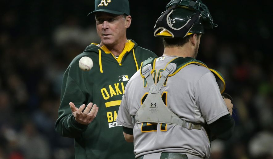 FILE - In this Oct. 3, 2015, file photo, Oakland Athletics manager Bob Melvin, left, tosses the baseball as he waits with catcher Stephen Vogt for pitcher Daniel Coulombe to replace Arnold Leon on the mound in the sixth inning of a baseball game,  in Seattle. Manager Bob Melvin has been forced to recall all those demoralizing one-run losses by the Oakland Athletics last season, yet now he is able to envision far more favorable scenarios for 2016.(AP Photo/Ted S. Warren, File)