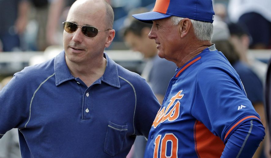 FILE - In this Wednesday, March 25, 2015 file photo, New York Yankees general manager Brian Cashman, left, talks to New York Mets manager Terry Collins before an exhibition baseball game in Tampa, Fla. For the first time in the four decades of baseball's modern economic era, the Yankees enter spring training without having signed a single free agent to a major league contract. (AP Photo/Kathy Willens, File)