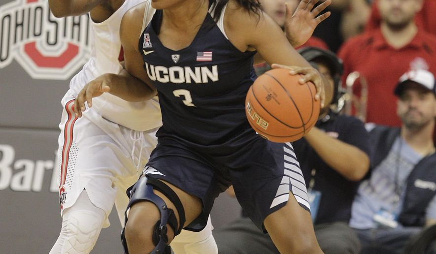 FILE - In this Nov. 16, 2015, file photo, Connecticut's Morgan Tuck posts up against Ohio State's Shayla Cooper during an NCAA college basketball game in Columbus, Ohio. Morgan Tuck believes her surgically repaired right knee only has a few more good years of basketball left in it.  That has the redshirt junior reconsidering whether she'll return to the Huskies for another season, or turn pro and make money playing basketball while she can. By Pat Eaton-Robb. 450 words. Upcoming by 5 p.m. With AP Photos (AP Photo/Jay LaPrete, File)