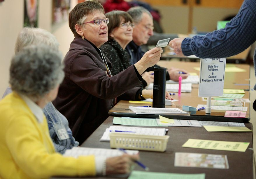 Chief inspector Jeanne Thieme inspects a voter's identification card at the Olbrich Gardens polling location in Madison, Wis. Tuesday, Feb. 16, 2016. The Supreme Court election was the only statewide race in Tuesday's primary, which included scattered county and municipal races. Turnout was projected at only around 10 percent. A photo ID was required to vote, a new requirement stemming from a law first passed in 2011 but eventually put on hold until it was upheld by the state Supreme Court in one of several rulings seen as partisan in recent years. (Michael P. King/Wisconsin State Journal via AP) MANDATORY CREDIT