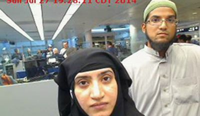 This July 27, 2014, file photo provided by U.S. Customs and Border Protection shows Tashfeen Malik, left, and Syed Farook, as they passed through O'Hare International Airport in Chicago. (U.S. Customs and Border Protection via AP)