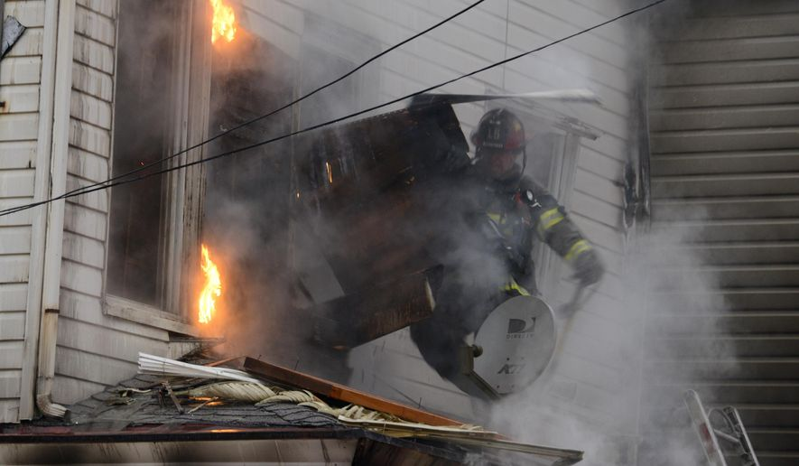 A City of Pittsburgh firefighter pulls back siding on the second floor to expose fire at the scene of a fatal fire at a boarding house in Pittsburgh, Wednesday, Feb. 17, 2016. Fire Chief Darryl Jones said heavy flames were visible when crews arrived, and the fire was so intense that it set off an alarm next door. (Darrell Sapp/Pittsburgh Post-Gazette via AP) MAGS OUT; NO SALES; MONESSEN OUT; KITTANNING OUT; CONNELLSVILLE OUT; GREENSBURG OUT; TARENTUM OUT; NORTH HILLS NEWS RECORD OUT; BUTLER OUT; MANDATORY CREDIT
