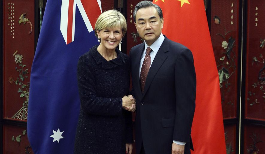 Australian Foreign Minister Julie Bishop, left, and Chinese Foreign Minister Wang Yi pose for photographers as she arrives for a meeting at the Ministry of Foreign Affairs in Beijing, Wednesday, Feb. 17, 2016. China's moves to assert its sovereignty claims in the South China Sea are expected to be a key agenda item during a visit to Beijing Wednesday by Bishop. (Wu Hong/Pool Photo via AP)