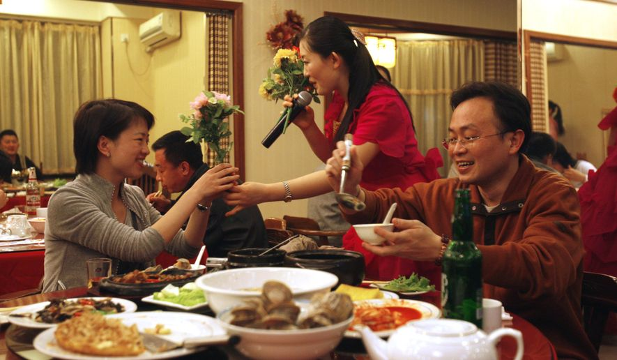FILE - In this April 5, 2009, file photo, a North Korean singer presents flowers to a customer at a North Korean restaurant in Dandong in northeastern China's Liaoning province. South Koreans have been told not to eat at North Korea's restaurants around the world, although such visits aren't illegal, the South's Foreign Ministry said Wednesday, Feb 17, 2016. (AP Photo/Ng Han Guan, File)