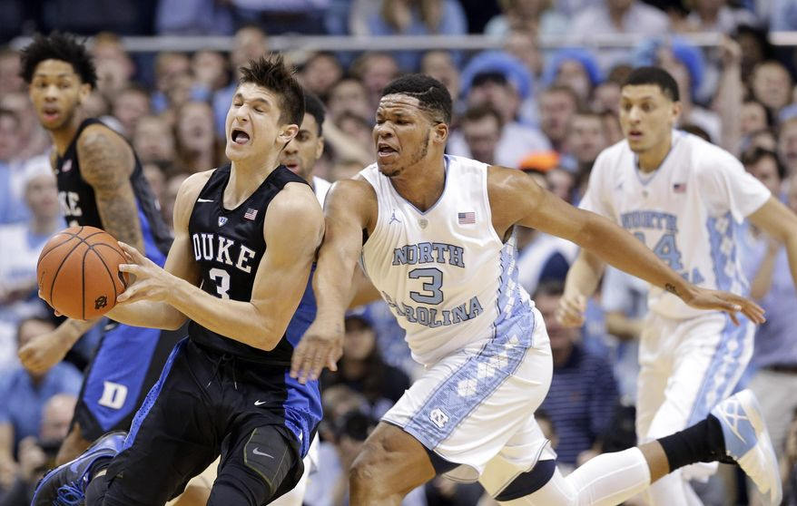 North Carolina's Kennedy Meeks, right front, and Duke's Grayson Allen, left, chase the ball during the first half of an NCAA college basketball game in Chapel Hill, N.C., Wednesday, Feb. 17, 2016. (AP Photo/Gerry Broome)