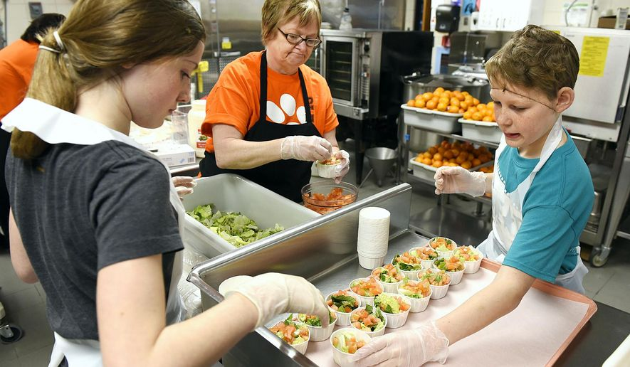 ADVANCE FOR SATURDAY FEB. 20 AND THEREAFTER - Head Cook Judy Hommerding, center, works with sixth-grade students Grace Gilmor, 12, left, and Jonathon Becker, 12, Thursday, Feb. 11, 2016,  to get ready for lunch at Clearview Elementary School, in Clear Lake, Minn. Students volunteer for a program to help the kitchen staff on a rotating basis. (Jason Wachter/St. Cloud Times via AP)
