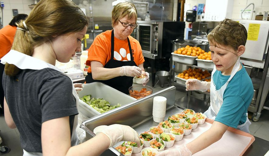 In this file photo from Feb. 11, 2016, elementary school students in Minnesota help a cafeteria worker prepare lunch.  (Jason Wachter/St. Cloud Times via AP) **FILE**