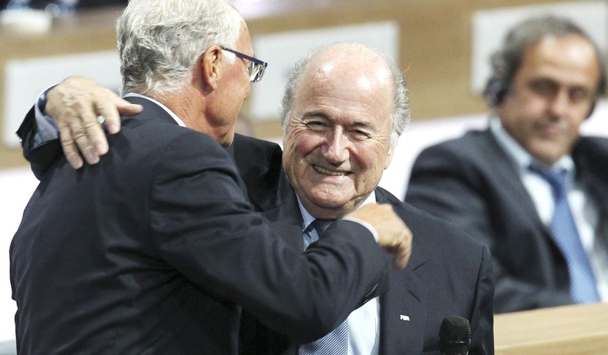 FILE - In this June 1, 2011 file photo FIFA President Joseph Blatter reacts when is hugged by German soccer legend Franz Beckenbauer, left, after he was re-elected FIFA president  in Zurich, Switzerland. The adjudicatory chamber of FIFA's Ethics Committee on Thursday, Feb. 17, 2016 has imposed a sanction of a warning and fine of 7000 Swiss francs (US$ 7050) on Beckenbauer for failing to cooperate with an Ethics Committee investigation. (AP Photo/Michael Probst, file)