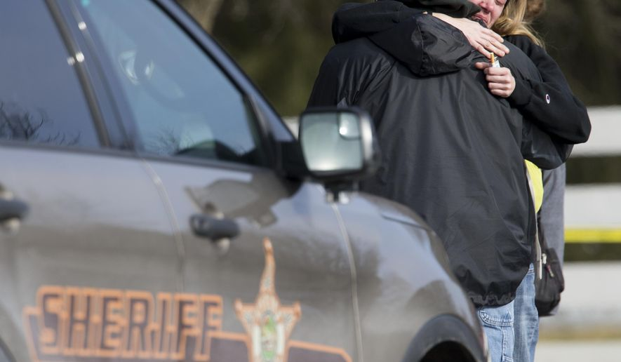People hug near a home where a woman and her son were fatally shot, in Zionsville, Ind., Wednesday, Feb. 17, 2016. A man wanted in connection with the fatal shootings of his niece and her young son in suburban Indianapolis killed himself Wednesday afternoon at a downtown Indianapolis hotel, police said. (Robert Scheer/The Indianapolis Star via AP)  NO SALES; MANDATORY CREDIT