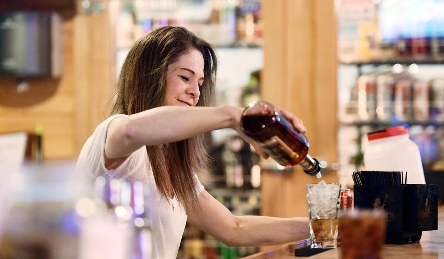 ADVANCE FOR SATURDAY, FEB. 20 - Jen Shaul, a bartender at Buck's Saloon in Melba, Idaho, pours whiskey at the bar Feb. 6, 2016. Voters in Melba voted last November to allow liquor to be sold by the glass. (Adam Eschbach/Idaho Press-Tribune via AP)