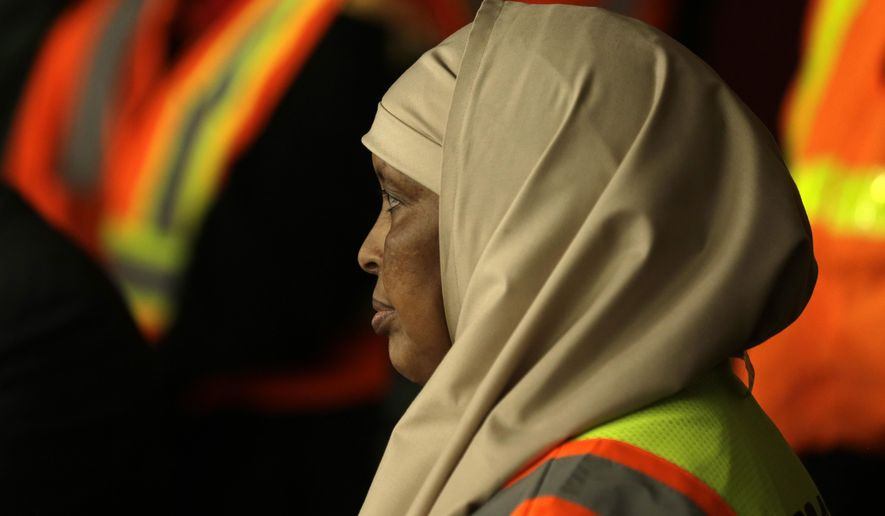 Aneb Abdinor Hirey, who works as a driver at the Seattle-Tacoma International Airport rental car facility, listens to questions, during a news conference Wednesday, Feb. 17, 2016, in Seattle. More than a dozen workers at Seattle-Tacoma International Airport filed lawsuits on Wednesday over the $15 minimum wage they say they have not been paid. Turner said the employees are owed as much as $20,000 each in back pay since the higher wage went into effect more than two years ago. (AP Photo/Ted S. Warren)