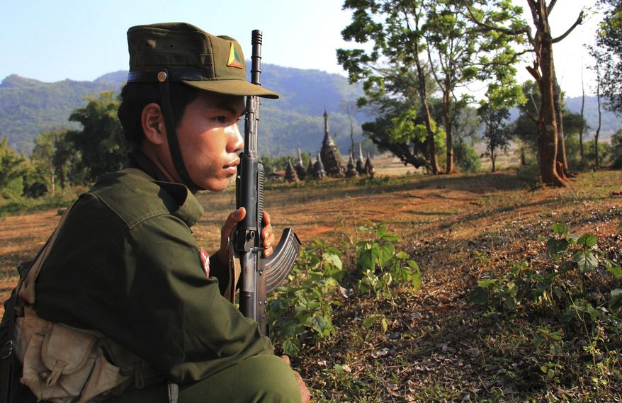In this Feb. 4, 2016, photo, a rebel fighter of the Shan State Army North (SSA-N) stands guard close to the front line of the fighting area in Mong Ark, in an area under the control of SSA-N in northeastern Shan state, Myanmar. Myanmar's civil war - the longest in modern world history - hasn't ended, even with democracy triumphant in recent elections and the winner, Aung San Suu Kyi, pledging to end hostilities between the central government and a host of autonomy-seeking ethnic minorities. Prospects for stopping the bloodshed are balanced on a knife's edge. (AP Photo/Esther Htusan)