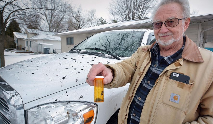In a photo from Sunday, Feb. 14, 2016, Paul Schlutow holds a pill container of black residue scraped off his Doge Ram truck in Harrison Township, Mich. Residents of the suburban Detroit community want to know how a black, oily substance ended up splashed on their homes, vehicles and property. (Ray Skowronek/The Macomb Daily via AP)