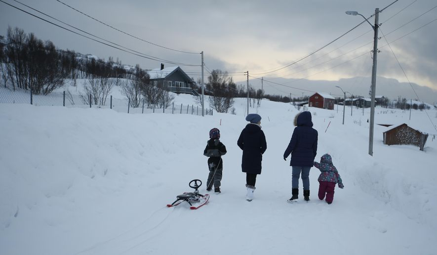 in this photo taken Tuesday, Feb. 2, 2016, asylum seekers take their children fro a walk  near the temporary accommodation at  the Altnes camp on the island of Seiland, northern Norway. (AP Photo/Alastair Grant)