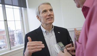 Sen. Rob Portman, R-Ohio, speaks to a reporter during the Queen City Mobile Summit at Union Hall, Wednesday, Feb. 17, 2016, in Cincinnati. (AP Photo/John Minchillo) ** FILE **