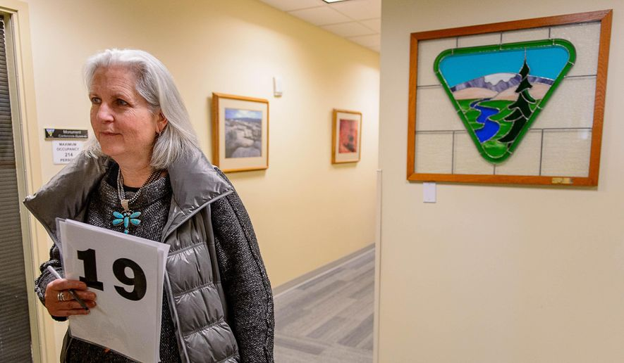 In this Tuesday Feb. 16, 2016 photo, environmental writer Terry Tempest Williams with her bidding number walks on the hallway of the Bureau of Land Management's Salt Lake City office. Oil and gas industry officials have said environmental writer Tempest Williams' bid on at least 800 acres is insignificant. (Trent Nelson/The Salt Lake Tribune via AP) MANDATORY CREDIT