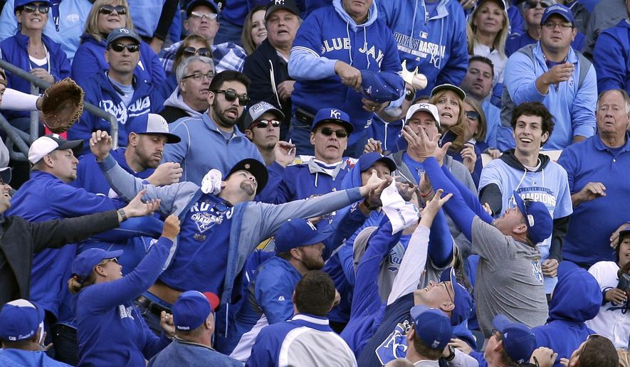 FILE - In this Oct. 17, 2015, file photo, fans reach after a foul ball hit by Toronto Blue Jays' Ben Revere during the third inning in Game 2 of baseball's American League Championship Series against the Kansas City Royals in Kansas City, Mo. The Royals are installing additional netting at Kauffman Stadium that extends toward the outfield end of each team's dugout to improve the safety for fans sitting along the foul lines.(AP Photo/Charlie Riedel, File)
