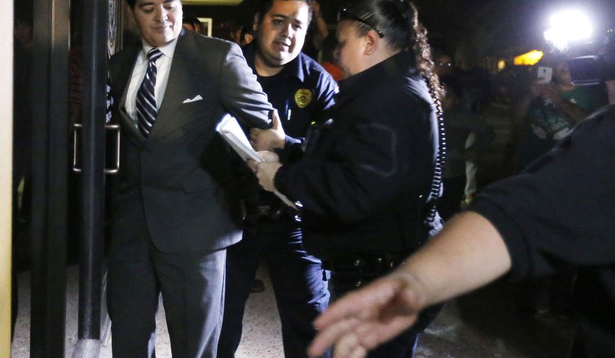 In this photo taken on Tuesday, Feb. 16, 2016, Crystal City Mayor Ricardo Lopez is taken away from city hall by police, in Crystal City, Texas,  after allegedly disrupting a City Council meeting while fighting a recall effort that began before his indictment this month in a public corruption investigation that has ensnarled him and most of the council. (Kin Man Hui /The San Antonio Express-News via AP) RUMBO DE SAN ANTONIO OUT; NO SALES; MANDATORY CREDIT