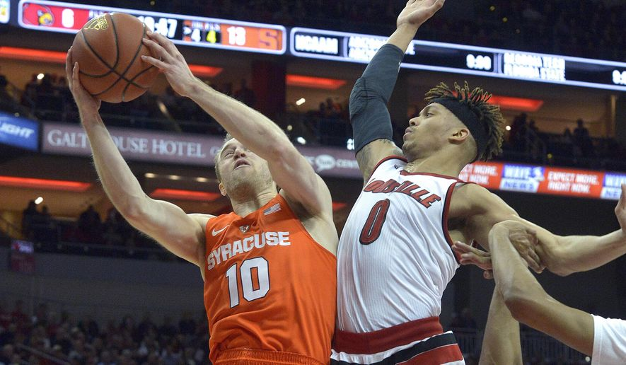 Syracuse's Trevor Cooney (10) attempts a shot over the defense of Louisville's Damion Lee (0) during the first half of an NCAA college basketball game, Monday, Feb. 17,  2016, in Louisville Ky. (AP Photo/Timothy D. Easley)