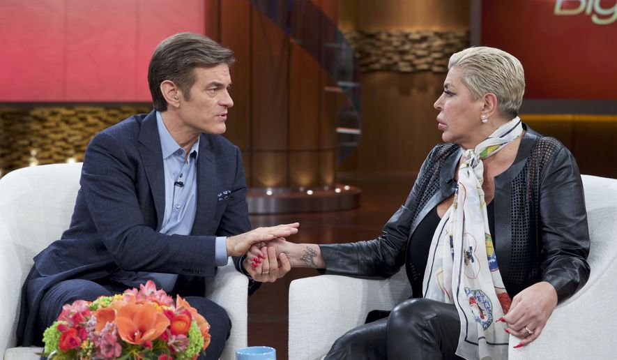 """In this image released by The Dr. Oz Show, Dr. Mehmet Oz, left, holds the hand of Angela """"Big Ang"""" Raiola during a taping of """"The Dr. Oz Show,"""" in New York. (The Dr. Oz Show via AP)"""