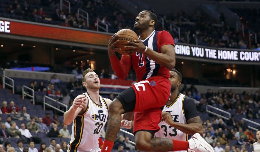 Washington Wizards guard John Wall (2) drives to the basket in front of Utah Jazz forward Gordon Hayward (20) and forward Trevor Booker (33) during the first half of an NBA basketball game Thursday, Feb. 18, 2016, in Washington. (AP Photo/Alex Brandon)