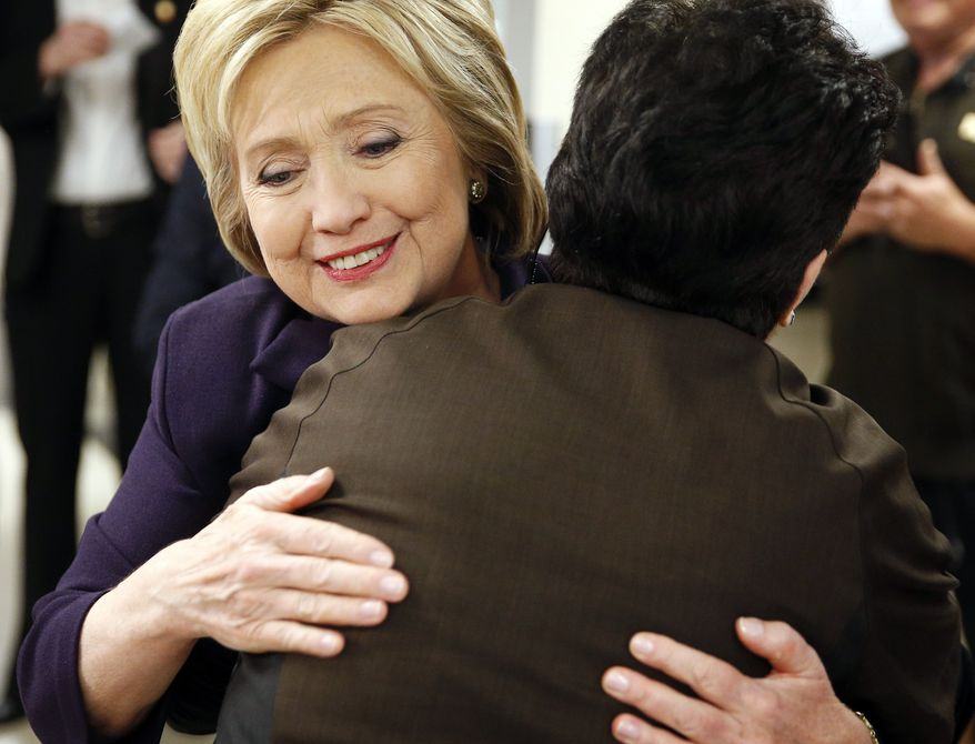 Democratic presidential candidate Hillary Clinton hugs an employee of Paris Las Vegas during a visit to the hotel and casino Thursday, Feb. 18, 2016, in Las Vegas. (AP Photo/John Locher)