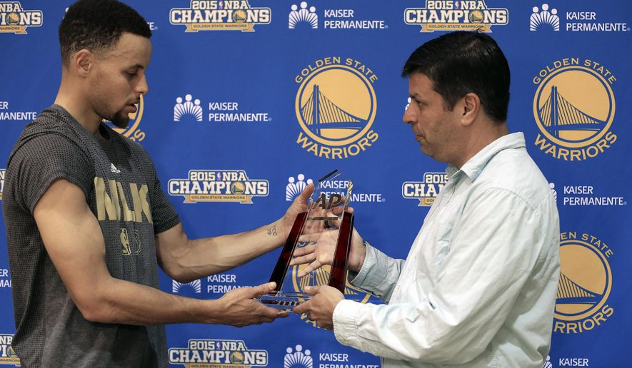 Golden State Warriors' Stephen Curry, left, accepts the AP Male Athlete of the Year award from Associated Press sports writer Josh Dubow Thursday, Feb. 18, 2016, in Oakland, Calif. (AP Photo/Ben Margot)