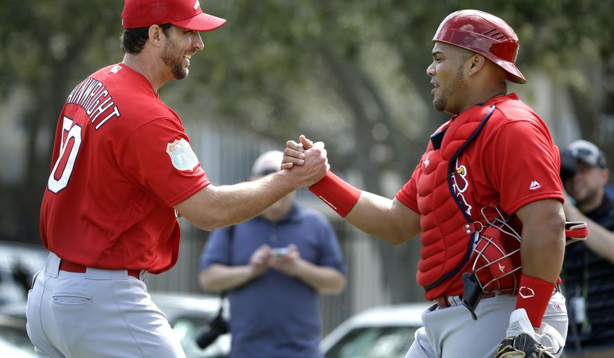 St. Louis Cardinals pitcher Adam Wainwright, left, shakes hands with catcher Brayan Pena after throwing a bullpen session during spring training baseball practice Thursday, Feb. 18, 2016, in Jupiter, Fla. (AP Photo/Jeff Roberson)