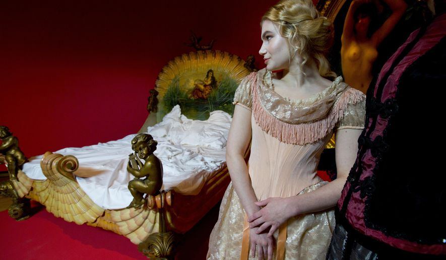Models pose next to a 19th century bed of a French courtesan during a photo call for the upcoming exhibit Easy Virtue at the Van Gogh Museum in Amsterdam, Netherlands, Tuesday, Feb. 16, 2016. The exhibit, which runs from Feb. 19 till June 19 2016, shows prostitution through the eyes of Vincent van Gogh and many other well-known 19th-century artists, including Edgar Degas, Henri de Toulouse-Lautrec and Pablo Picasso. (AP Photo/Peter Dejong)