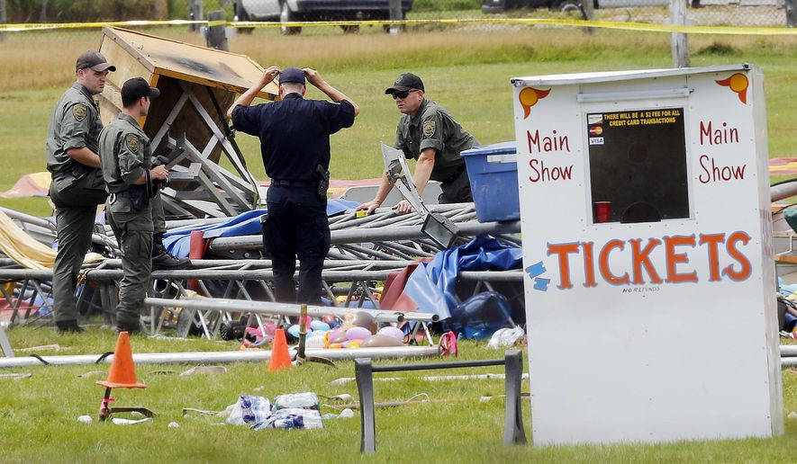 FILE - In a Aug. 4, 2015 file photo, investigators work at the scene of a circus tent that collapsed, killing a father and his 6-year-old daughter in Lancaster, N.H. Federal safety officials have proposed more than $33,000 in fines against a Florida-based circus operator for the tent collapse. The Occupational Safety and Health Administration said Thursday, Feb. 18, 2016, that Sarasota-based Walker International Events failed to properly erect the tent and ignored severe weather and high-wind warnings from the National Weather Service. (AP Photo/Jim Cole, File)